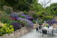 A patio dining terrace alongside a large bank planted with perennials and ornamental grasses. Planting includes: Salvia 'Caradonna', Geranium 'Rozanne', Campanula persicifolia, Alchemilla mollis, Penstemon 'Garbet' and Molinia 'Karl Foerster'.