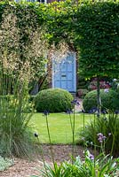 Moleshill garden with a view through Stipa gigantea and pleached trees to topiary box and front door beyond.