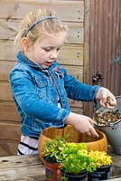 Child planting thyme in a recycled wooden bowl. Add gravel to the bottom of the bowl, to improve drainage and prevent earth seeping out through the holes.
