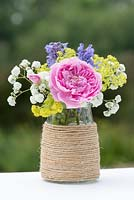 A colourful summer posie with pink rose, alchemilla, baby's breath and catmint in a glass jar decorated with twine.
