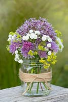 A summer posie with alliums, gypsophila and alchemilla in a glass gar decorated with twine.