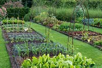 Kitchen garden with raised beds of lettuces, cabbages. beans, spinach, sweet corn, carrots, beetroot and marigolds.