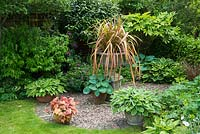 Hosta collection arranged in corner of garden around phormium in stone urn with background of shrubs including elaeagnus, fatsia, philadelphus and griselinia.