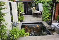 Outdoor dining area on a small patio with pergola covered with Parthenocissus. Agapanthus orientalis White in pot. Carpinus betulus - Hornbeam in modern pots. Pond with Koi Carp. Family Fabry - Mathijs. Belgium