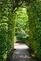 Hornbeam arch with stone bench backed by Buxus sempervirens in the background - June, Le Jardin de Marguerite, France
