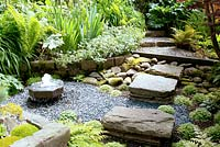 Stepping stones over shaded sunken gravelled area with small stone water feature leading to steps and raised herbaceous borders in July
