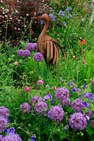 Drifts of Allium aflatunenese and Geranium ibericum lead the eye up to a rusted bird sculpture that forms an eye catcher in a border. June. Worcestershire
