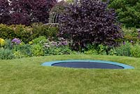 A trampoline set in a raised circle of lawn so that from a distance it is largely concealed.