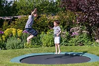 Oscar, 9, and 7-year-old Archie on the trampoline, set into the lawn.