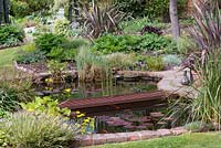 A brick edged fish pond with rusted metal bridge.