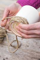 Carefully wrap the rope around the pot, using your spare hand to hold the rope in place