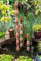 A small raised pond with stacked terracotta pots as a focal point.