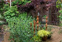 A gravel garden with terracotta pot sculpture, Cerinthe major var. purpurescens and Hakonchloa macra 'Aurola' in pots.
