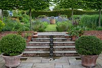 A contemporary, pumped water feature carries water down the steps to a small pebble pool. Above, pleached hornbeams frame views of perennial borders.