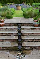 A contemporary, pumped water feature carries water down the steps to a small pebble pool.