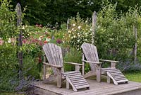 Two ariondack chairs on a raised deck in front of 'Bessie's End' - an informal parterre with wildflowers, lupins and Rosa 'Mme Alfred Carriere' weeping standards.