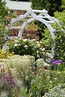 Border detail with ornate white arch, Euphorbia Silver Swan and Rosa Penelope