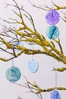 Painted Clay decorations with imprints of Pine foliage, hanging from a branch covered in Lichen