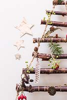 A hanging Christmas tree made with Birch branches. Decorations feature Pine cones, feathers, Rose hips and Ivy seed heads