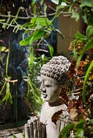 Detail of garden showing greenwall of various plants including begonia and succulents, with Buddha statue and incense.