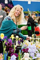Lady using a hairdryer to open iris buds on the Kelways stand. Chelsea Flower Show 2006