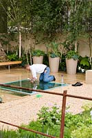Man wiping away muddy footprints. The Mencap and Cater Allen Bank Garden, Seeing the Whole Picture, Design Ruth Marshall, Chelsea Flower Show 2006