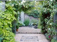 View through rose pergola to courtyard garden, pebble mosaic detail in path and water feature