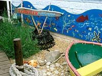 School playground garden - lobster lagoon.  Designer: Yvonne Mathews. Close up of small boat shingle and pebbles. Lavender  - lavendula planting, decking and ocean life mural in shape of wave and orange buoy.