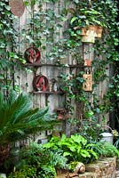Ornate items on shelves. Planting of: Hedera helix, Hosta 'Sum and Substance', Pseudopanax crassifolius, Equisetum, Cycas revoluta, Crytomium falcatum and wooden wall. Lucille Lewins small court yard garden in Chiltern street studios, London. Designed by Adam Woolcott and Jonathan Smith