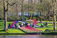 Visitors gather for pictures and selfies around one of the massed bulb displays at Keukenhof in Holland. To the right a father prevents his stroller from running away by using his foot as a brake.