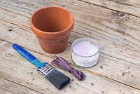 Painted Spring pots. Materials required are a paintbrush, coloured raffia, terracotta pot and whitewash or lime paint