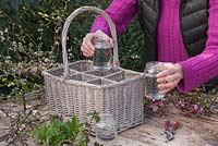 Place the jars with water into each section within the wicker basket