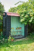 Mini garden pavilion with table and chairs and blue green interior.
