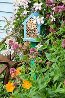 Wildlife gardening - early summer garden with pole mounted bug box placed in nectar rich area of garden.