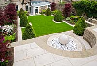 Contemporary urban garden on three levels featuring: marple sphere and pebble fountain and paved terrace, lawn, box pyramids, tulips and maples, basement seating area and conservatory