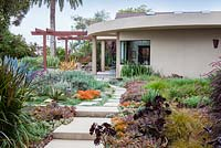 View across concrete path and mixed beds to modern house and outside eating area.  Debora Carl's garden, Encinitas, California, USA. August.