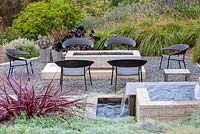 View of gas fired fire pit and outside seating. Debora Carl's garden, Encinitas, California, USA. August.