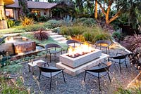 View of fire pit alight and outside seating area at night. Debora Carl's garden, Encinitas, California, USA. August.