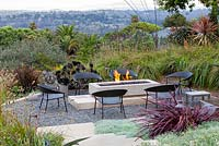 View of gas fired fire pit alight with outside seating. Debora Carl's garden, Encinitas, California, USA. August.