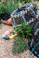 Seaside themed garden detail with buoy, crab and lobster pots, carex, gravel, driftwood, shells, ornaments, tradescantia, zalusianskya.