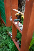 Wooden garden divider with niches for ornaments and found items including a tin aeroplane model, bottles and pebbles. Green foliage planting.