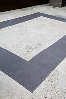 Rectangular design of slate paving set in white stone paving.