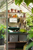 Interior of greenhouse with shelves, tools and pots