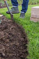 Brick Edging. Use the spade to dig 7 to 8 inches below ground level to create the foundations