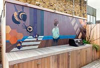 Painted mural by Lauren Mele behind bbq area of London roof terrace garden