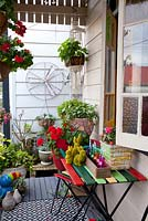 Front verandah of an inner city garden with three artificial grass rabbit ornaments, retro cement pots, box with coloured glass bottles with drinking straws and colourful outdoor table and chairs. A collection of pots and hanging baskets with a old fan blade and cover as a wall decoration, a retro cement pot planted with Spotted Dead Nettle, Lamium maculatum and a red flowered Pelargonium.
