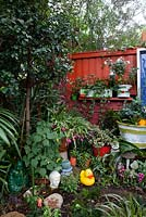 A collection of quirky pink coloured decorative objects in front of a small metal sign, including a Buddha, a duck an owl and two Garden Gnomes.