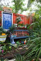 A painted garden bench in front of a collection of retro painted cement pots and a blue framed wall decoration.
