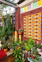 Inner city garden with ferns, cyclamens and bromeliads features colourful eclectic retro pieces sourced from local markets.