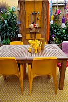Inner city garden with begonias and spathiphyllums features colourful eclectic retro pieces sourced from local markets, including a timber dining setting with assorted yellow objects